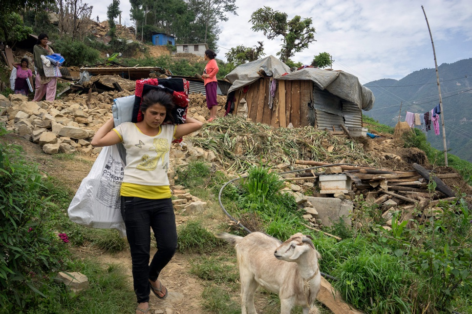 A young woman carries relief materials -- including a UNHCR plastic tarp and a hygiene kit -- in the hard-hit village of Jhankridanda, in Nepal's Lalitpur District.