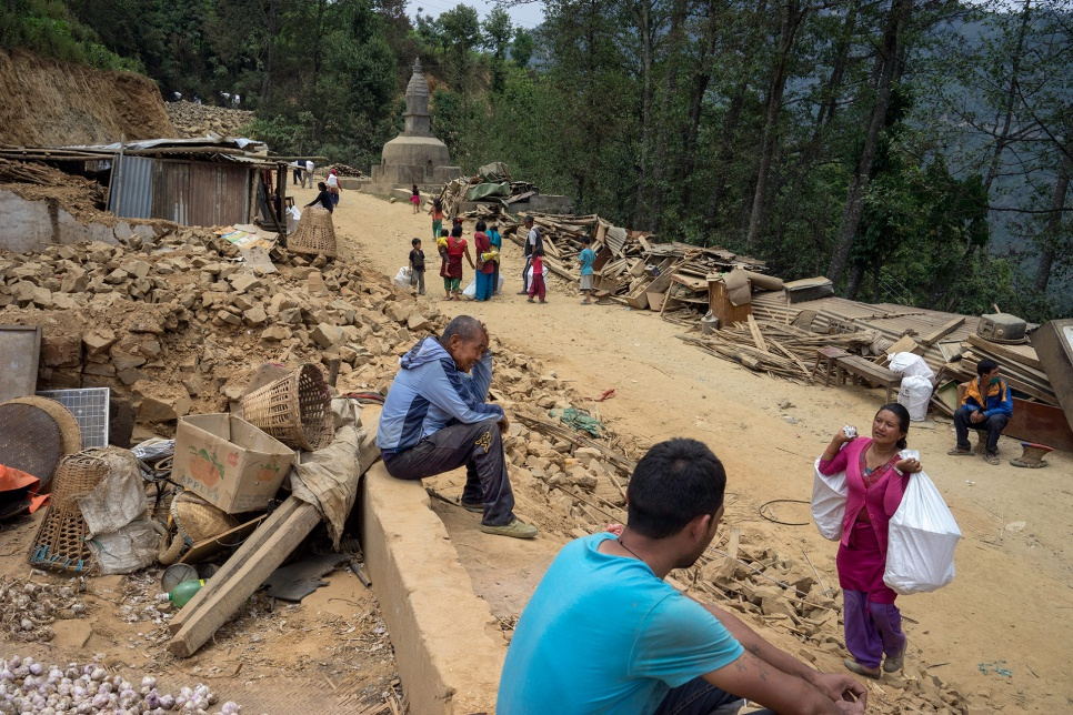 Dhan Bahadur Tamang, 66, sits in the rubble of his family's home along a roadside in the village of Jhankridanda, Lalitpur District, Nepal.