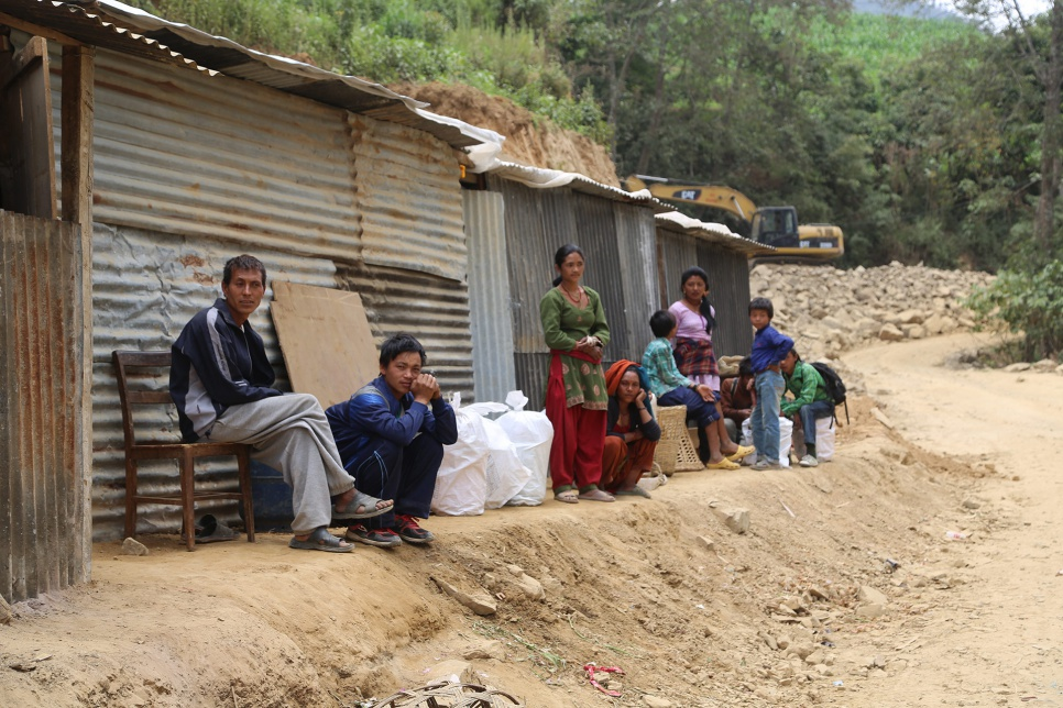 Dhan Bahadur Tamang's family now live in the corrugated iron shack on the far left, sharing a section of the narrow dirt road with two other families in Jhankridanda village.