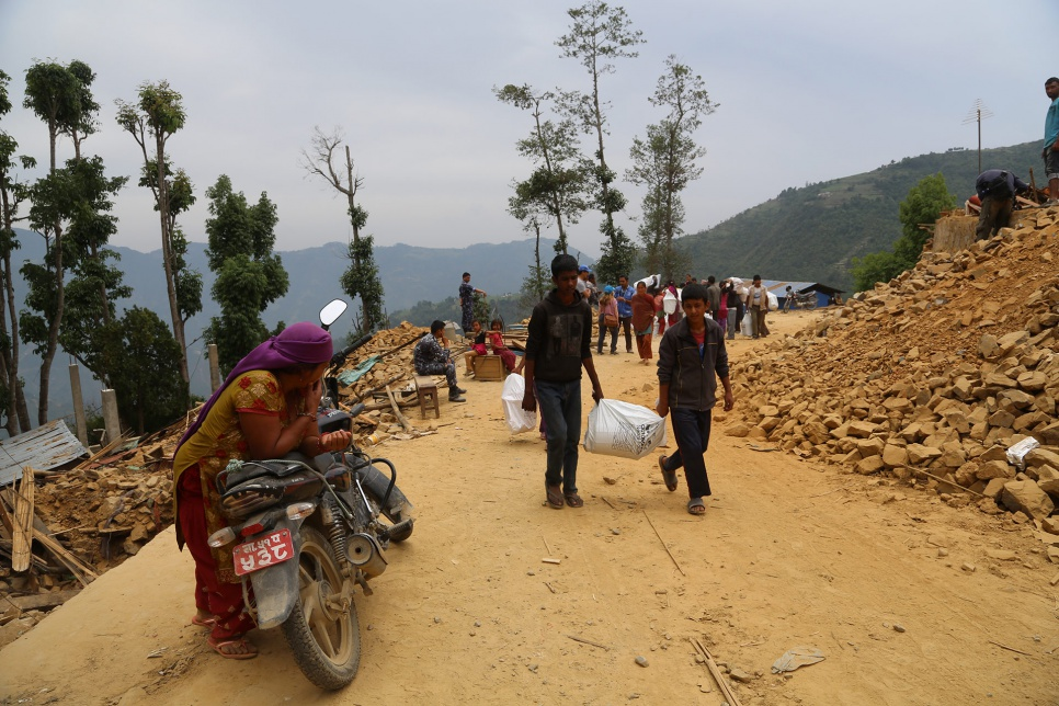 Two young Nepalis carry relief items back to the place where they have been sheltering since the devastating earthquake rocked Nepal on 25 April.