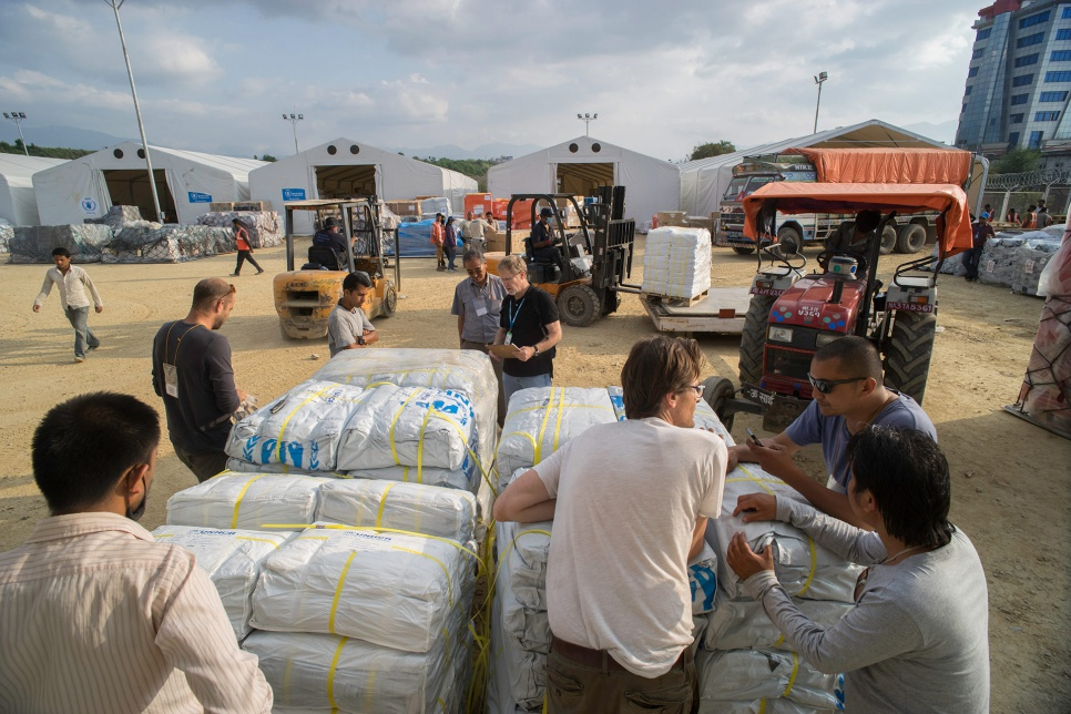 Aid workers from UNHCR and local partners, including volunteers from Yellow House, unload plastic tarps at the airport in Kathmandu, Nepal.