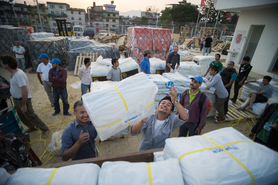 Volunteers working with UNHCR's local partners, including an organization known as Yellow House, load plastic tarps onto a truck to be distributed to affected communities across Nepal.