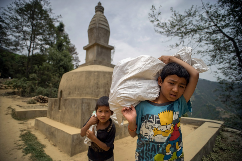 Sarod Tamang, 12, and Ramesh Ghalan, 7, carry tarps and other relief supplies past a Buddhist chorten, or stupa, following a distribution in Jhankridanda village, in Lalitpur District, Nepal.