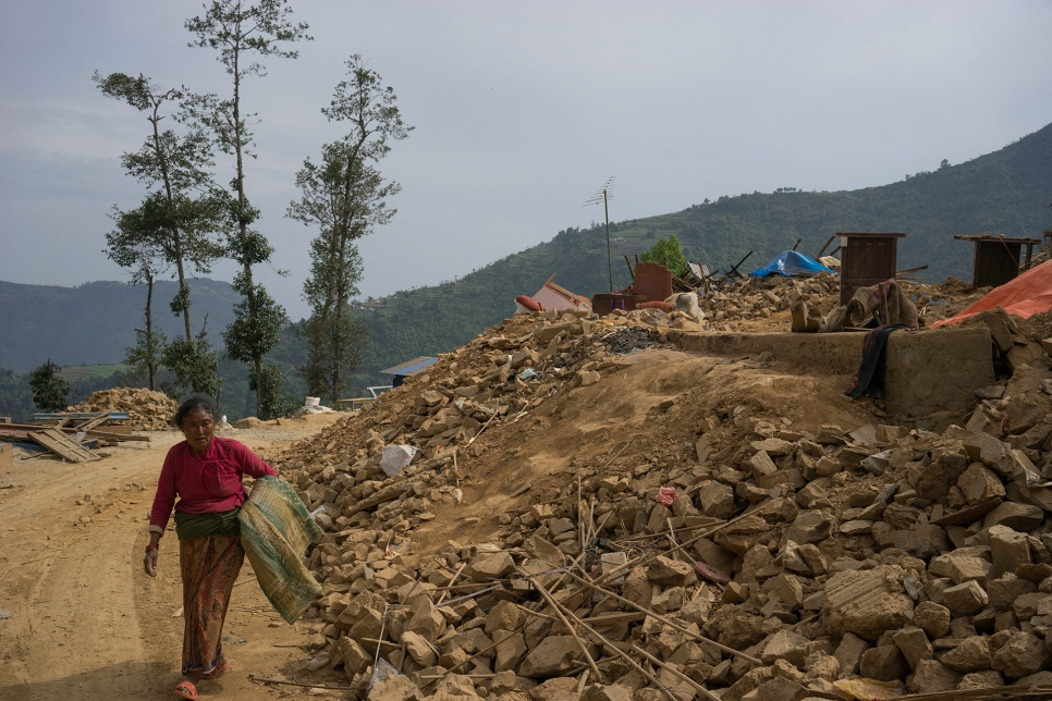 Shanti Lama, 54, the wife of Dan Bahadur Tamang, carries a mat salvaged from the rubble of her family's home in Jhankridanda village.