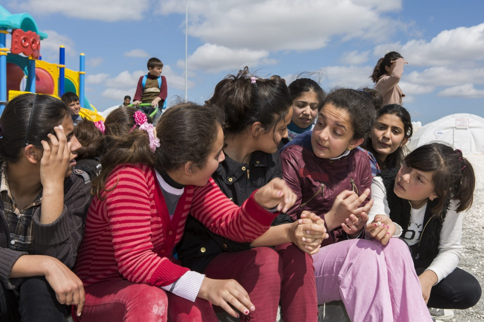 Ivra (wearing pink trousers) sits and talks with friends between classes outside a school in Suruç refugee camp in Turkey.