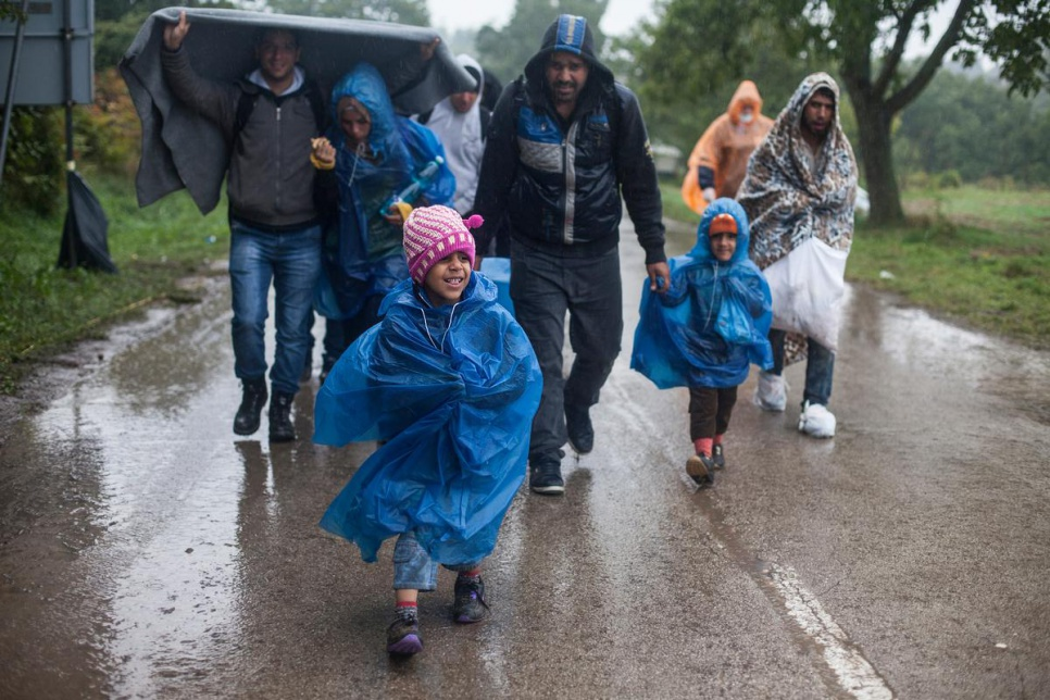 Refugees walk through the rain towards a bus that will transport them to Opatovac transit centre in Croatia.