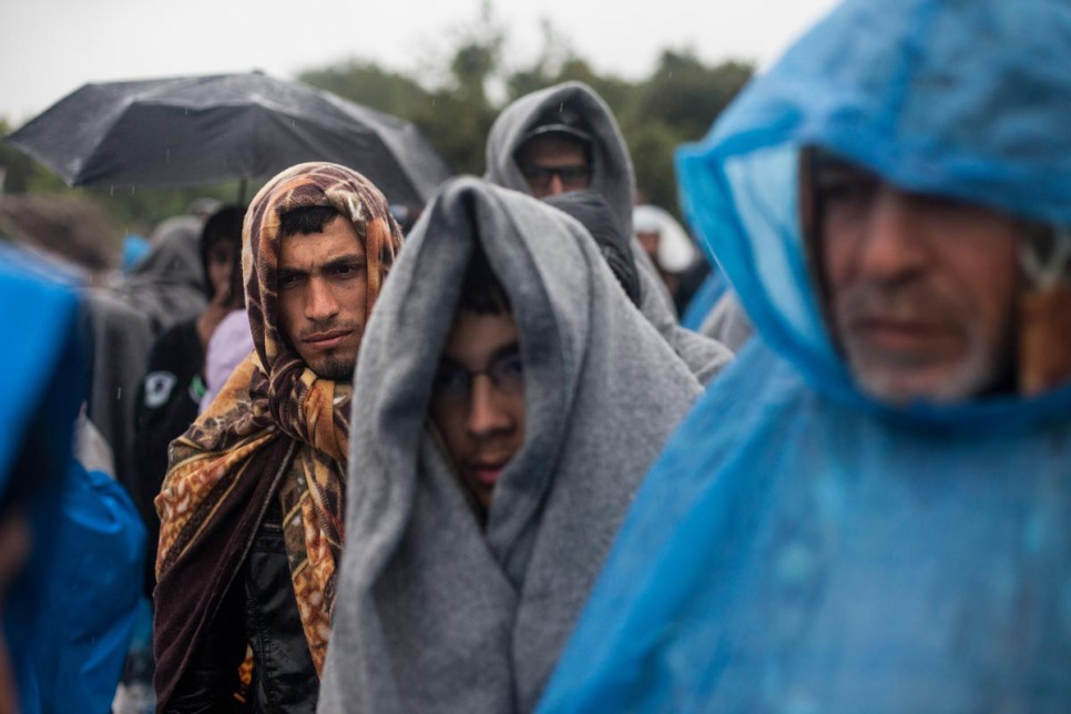 When supplies of rain ponchos run out refugees use blankets to protect themselves from the rain.
