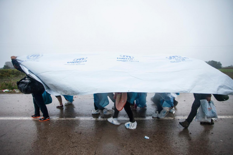 A group of refugees use UNHCR tents to protect themselves from rain in Bapska, Croatia.