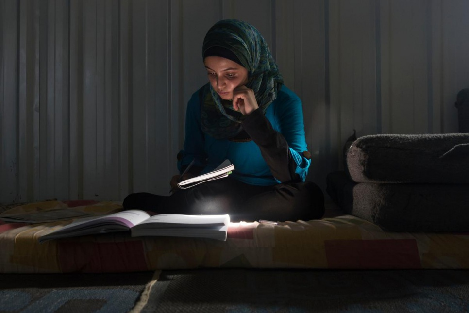 "Muzon studies in her home at Azraq camp. ""Our house was built by an engineer. When I was sick I went to a doctor. Education is everything in life,"" she says."