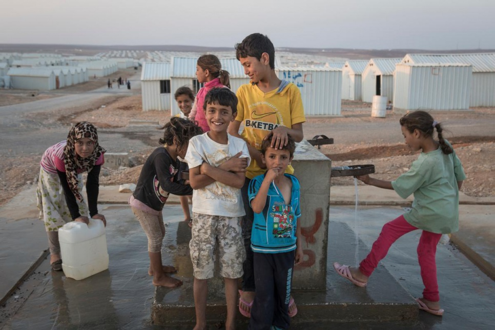 Syrian children getting water from a pump in Azraq camp.