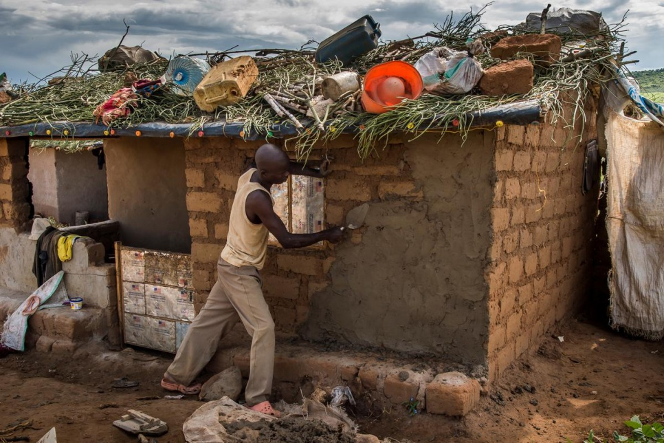 A newly arrived refugee renders the walls of his home in Kashojwa. Many refugees choose to use grass and other items to help waterproof the roofs.