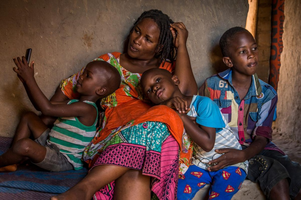 Burundian refugee Nbela, 30, sits with her sons, who range in age from four and 12. Together with her sister Odette, she runs a restaurant in Kashojwa.
