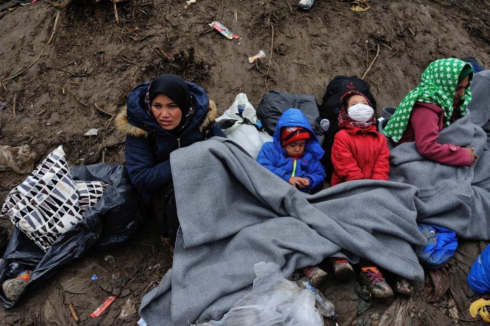 A mother and her children huddle under blankets in the mud at the Serbian border with Croatia. UNHCR distributes blankets and tents to help refugees keep warm, especially women, children and the elderly.