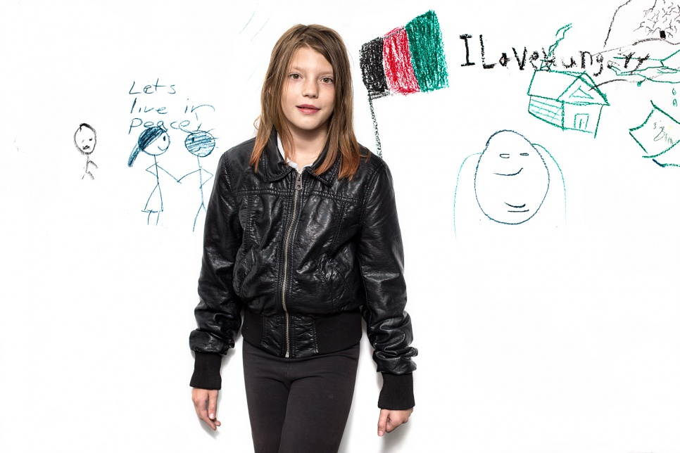 "Váczy Laura, 10, from Budapest, Hungary.<br><br>According to estimates, 2,000-3,000 Hungarian citizens, like Laura and her father, personally dropped by Keleti Station to offer snacks, water, clothes, shoes, bedding, tents and personal hygiene items for people in need. Laura drew the two figures beside her and wrote the line ""Let's live in peace."""