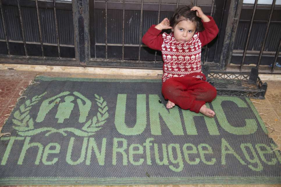 Syria / A Syrian displaced girl sitting on a UNHCR sleeping mat in this stadium which is a shelter for her and her family. Thousands of displaced families, mainly from Aleppo, are staying in makeshift shelters in Tartous that lack the basic services. The coastal city of Tartous on the Mediterranean, during the winter is usually wet with storms of heavy rain. UNHCR together with its implementing partners rushed to make these shelters ready for the rain season, through the winterization of the shelters and providing most needed core relief items including plastic sheeting, sleeping mats, blankets, mattresses, kitchen sets and hygiene kits. / UNHCR / B. Diab / November 2014