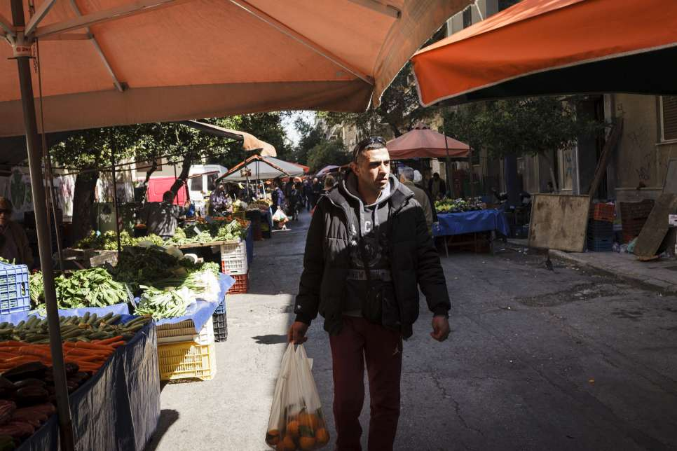 Ibrahim walks past street vendors selling fruit and vegetables at a market near his home in Athens.