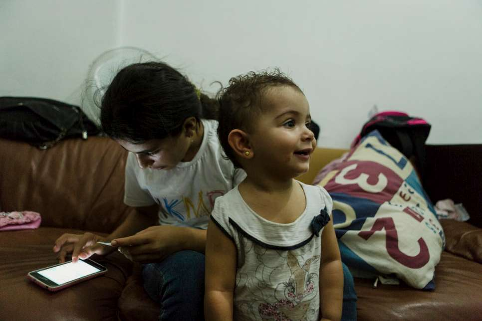 Hanan, 12, checks her phone while one-year-old Yara looks around the family apartment in downtown São Paulo, Brazil. Yara was born at Za'atari refugee camp in Jordan.