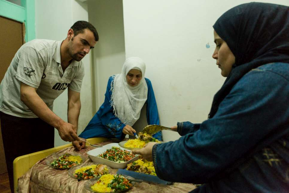 Yusra, 35, helps her sister-in-law serve dinner along with brother Zaher at the apartment they share with their families.