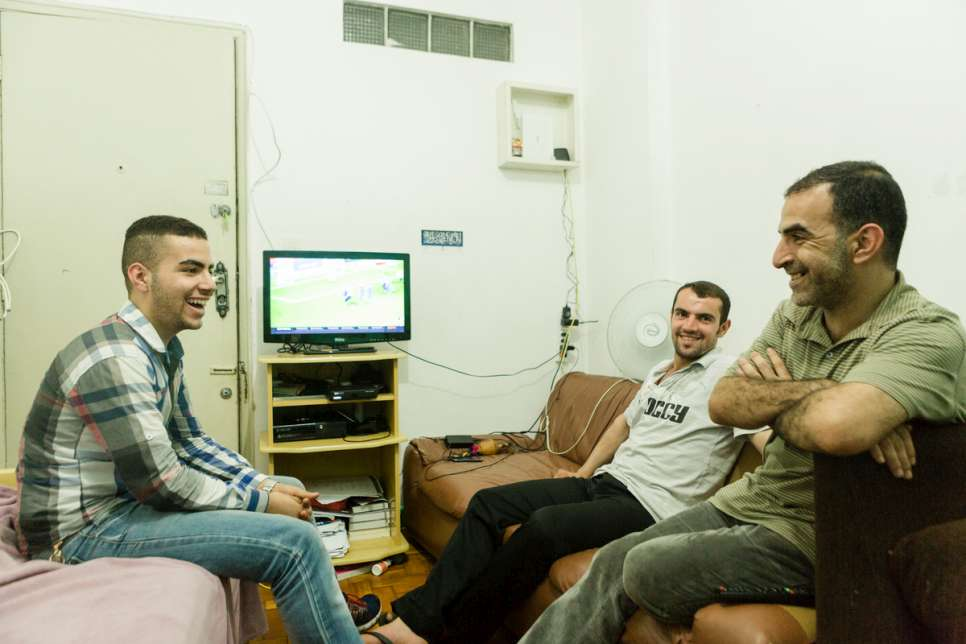 Moustafa (left) watches television with his uncle Zaher and father Khaled after the evening meal at their apartment.