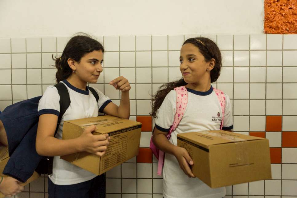Hanan collects her city-issued school uniform with new friend Andressa.