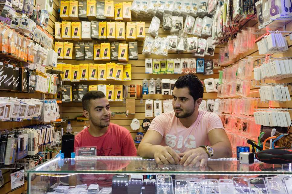 Moustafa, 16, works alongside his Lebanese boss, Hassan Salameh, 21, at a mobile phone acessories store in downtown São Paulo.
