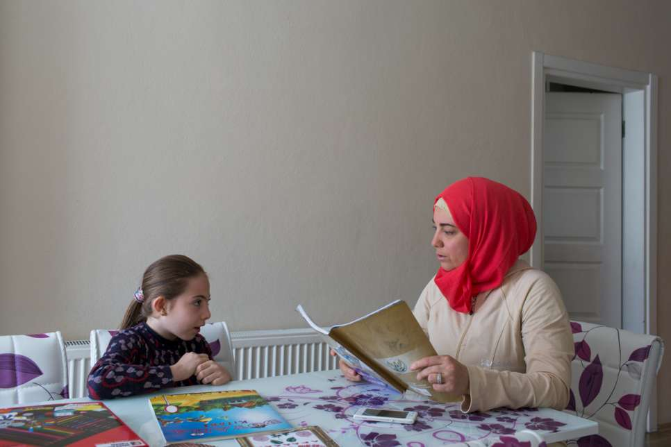 """I left Syria for the sake of my daughter,"" says Darie, who helps her daughter with her homework."