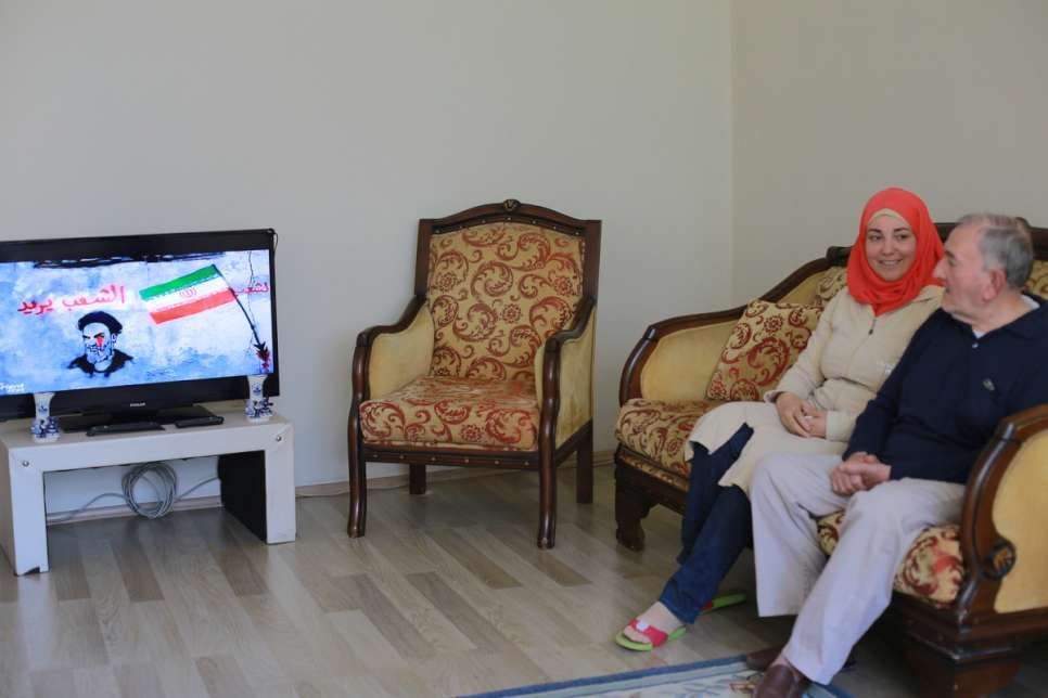 Darie keeps her father, Mahmud, 74, company as he watches Syrian news on television.