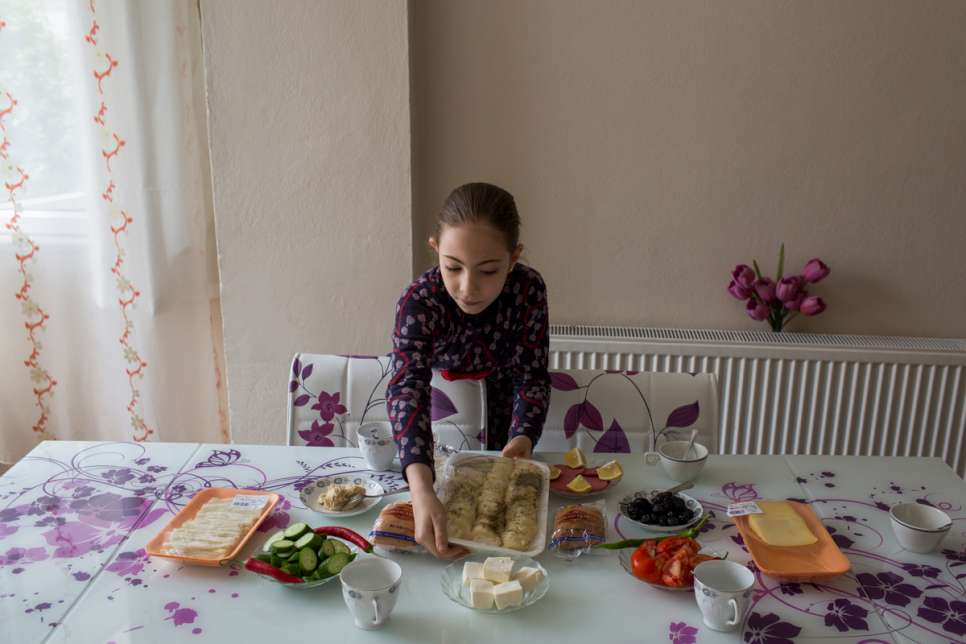 Mayas helps her mother, Darie, prepare breakfast at the apartment where they live in Istanbul.