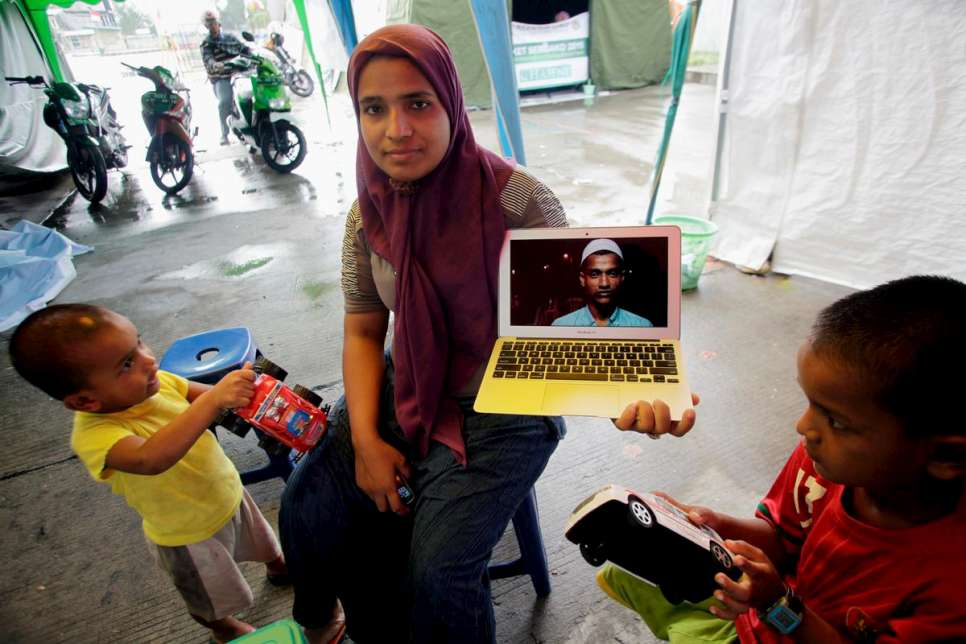 Fatima shows a photograph of her husband, Hassan, who is in Kuantan, Malaysia.