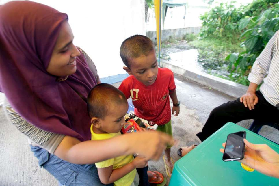 In Aceh, Indonesia, UNHCR staff show Fatima and her sons a photograph of her husband, Hassan, who is in Malaysia.