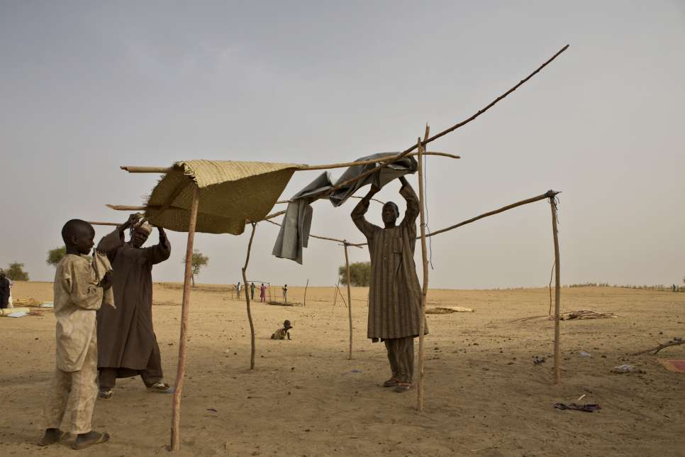 Mahamadou and Bala, helped by one of Bala's sons, build a shelter at the refugee camp in southern Niger.