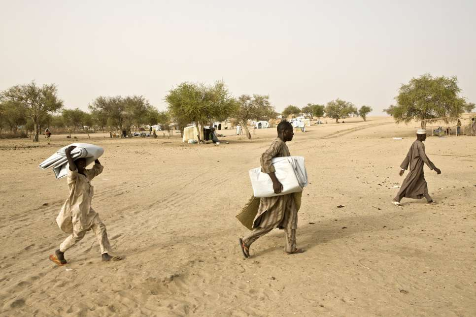 Bala, center, carries plastic sheeting to the spot allocated to his family to build their shelter at Sayam Forage camp in southern Niger.