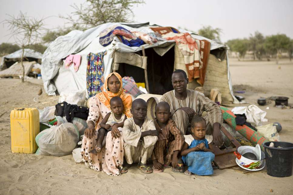 Bala poses with his wife Zara and their children in front of a temporary shelter they received upon their arrival in a refugee camp in southern Niger.