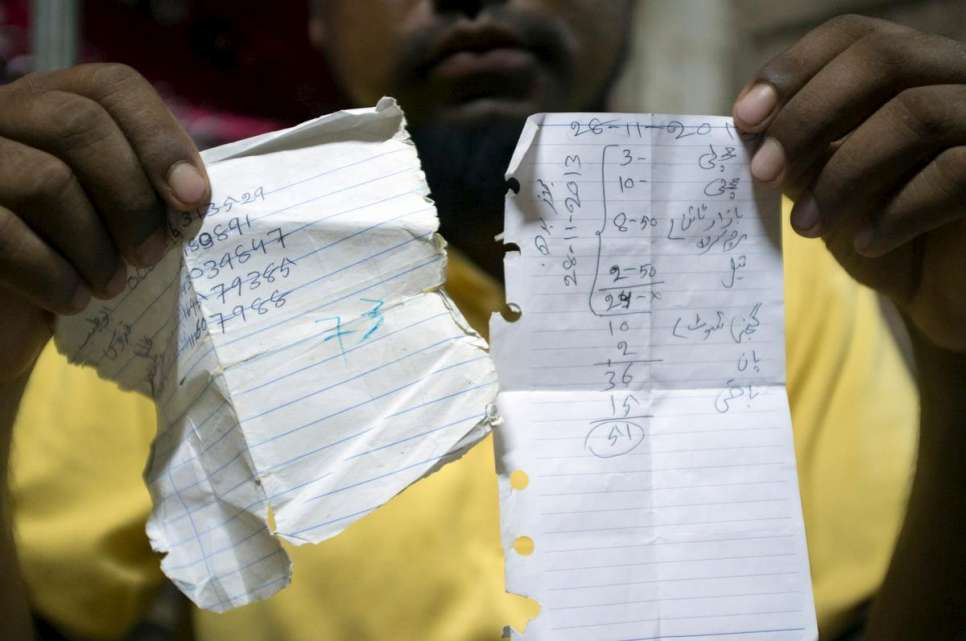 Abdul Rashid holds up notes he took during his journey on smugglers' boats from Maungdaw, Myanmar, to Kuantan, Malaysia, in late 2014.
