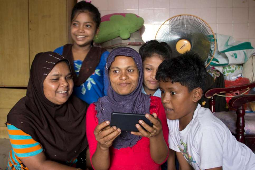 Rohima (centre) Skypes with her son Ali and daughter Shahida in Aceh, Indonesia. Her younger son, 10, looks on.
