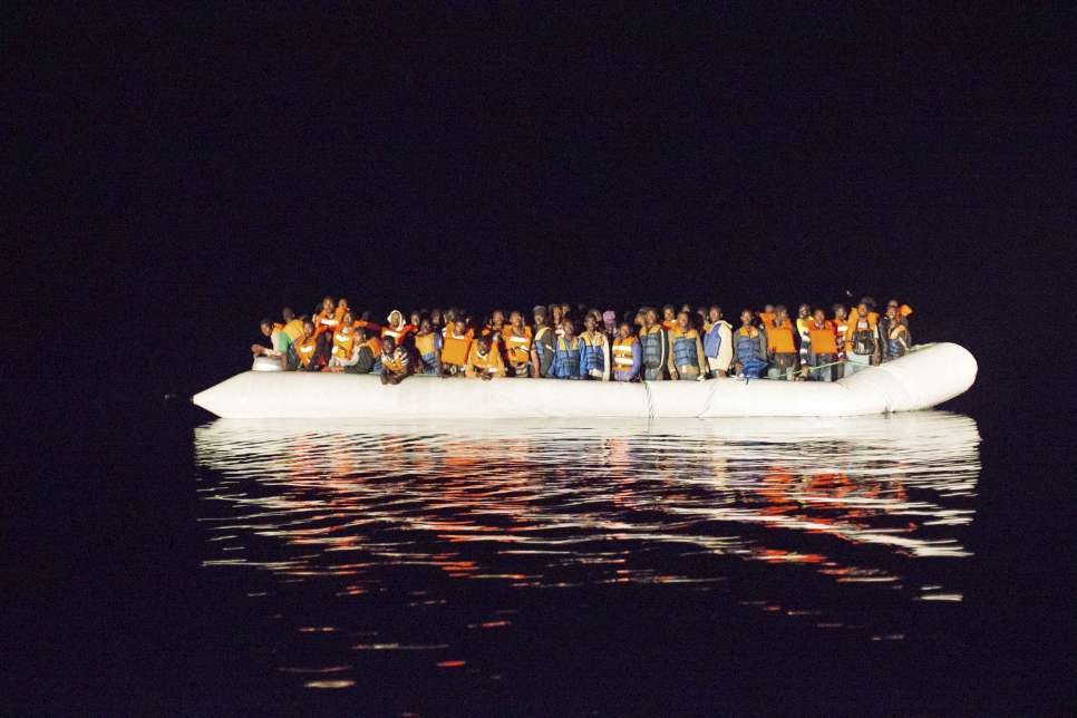 A boat filled with refugees and migrants crossing the Mediterranean floats off the coast of Italy.