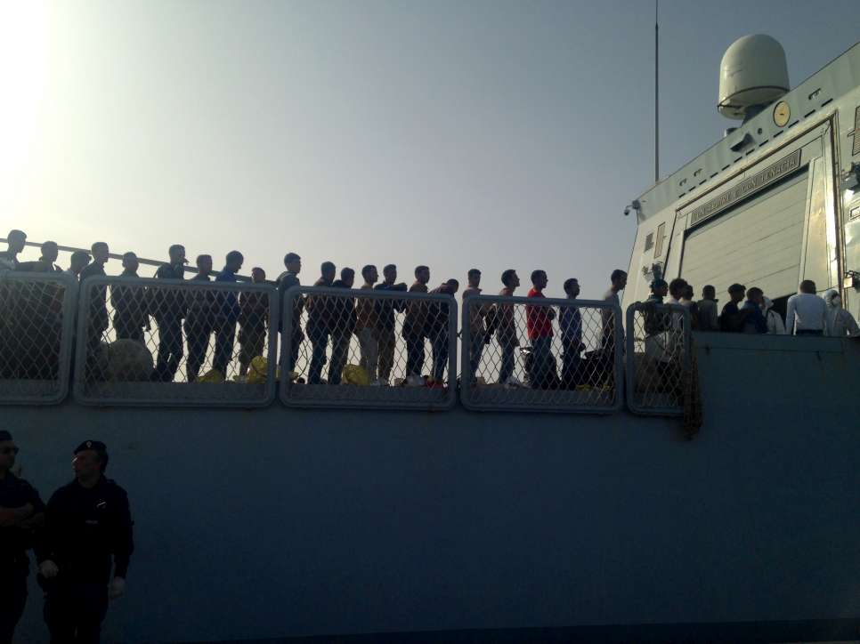 Refugees and migrants rescued from a shipwreck by the Italian Coastguard disembark in  