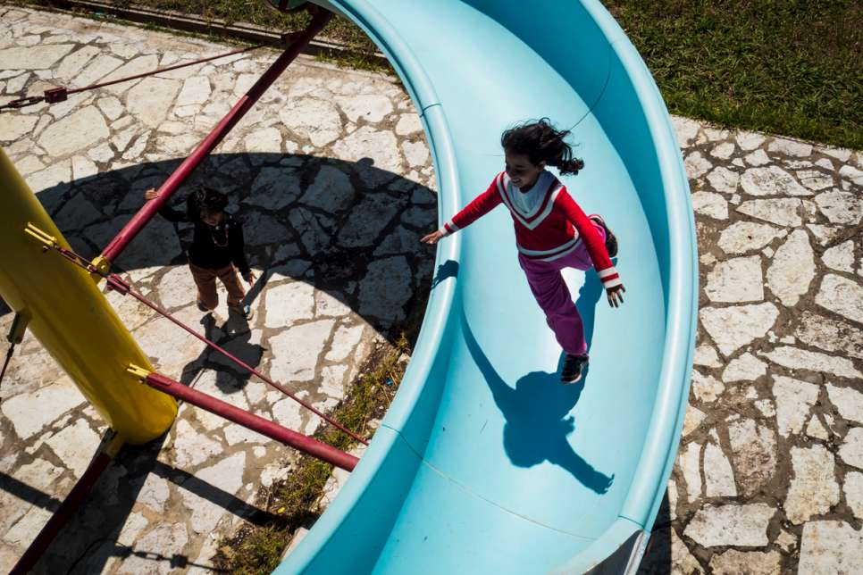 Syrian refugees Hala and Zeina play on a disused water slide inside LM Village.