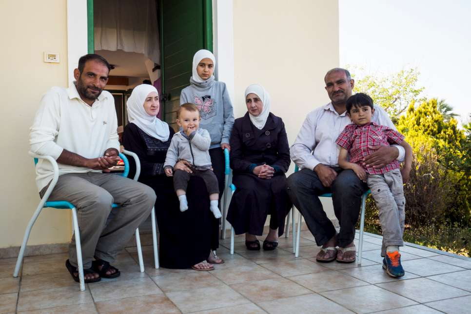 The Al Hamdan family sit outside the small bungalow they share at LM Village.