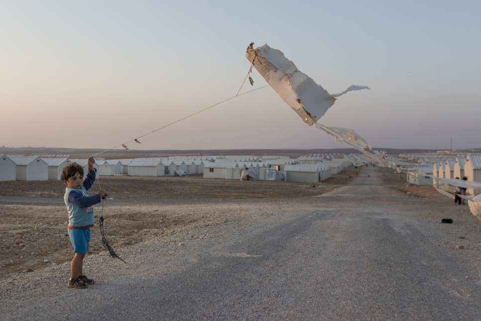 A Syrian boy flies a kite made from a piece of insulation at Azraq refugee camp in Jordan.