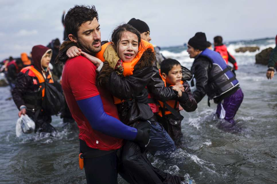 A volunteer lifeguard helps a young Afghan girl out of the sea on the Greek island of Lesvos.