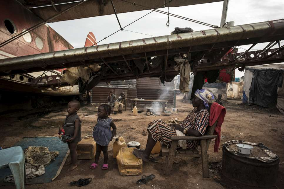 Displaced people live beneath a decommissioned airplane near the international airport in Bangui, Central African Republic.
