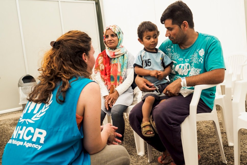 Ghulam Ali Jaffari, his wife Nabila, and their two-year-old son Amir talk with UNHCR staff while waiting to collect their newly issued ID's by the Greek Asylum Service.