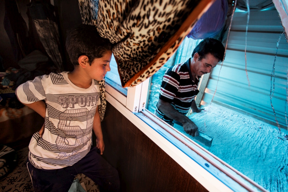"Faris watches from the bedroom as his father Abu Rabee' cuts ""raha"" into small pieces at his caravan at Za'atari refugee camp."