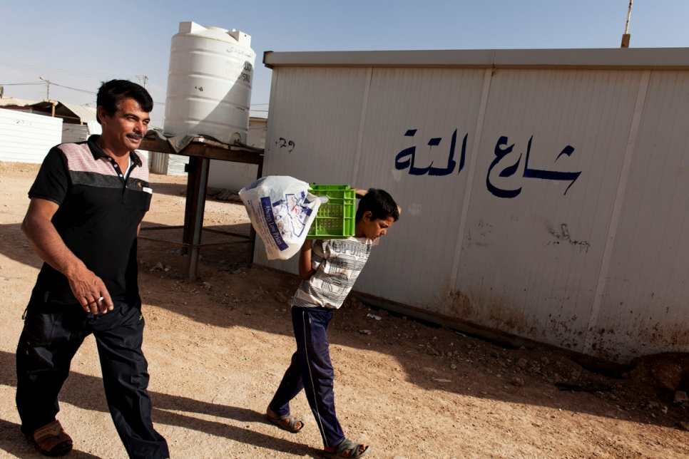 "Faris helps his father, Abu Rabee', by carrying the box of ""raha"" sweets to the market in the main shopping street at Za'atari refugee camp."