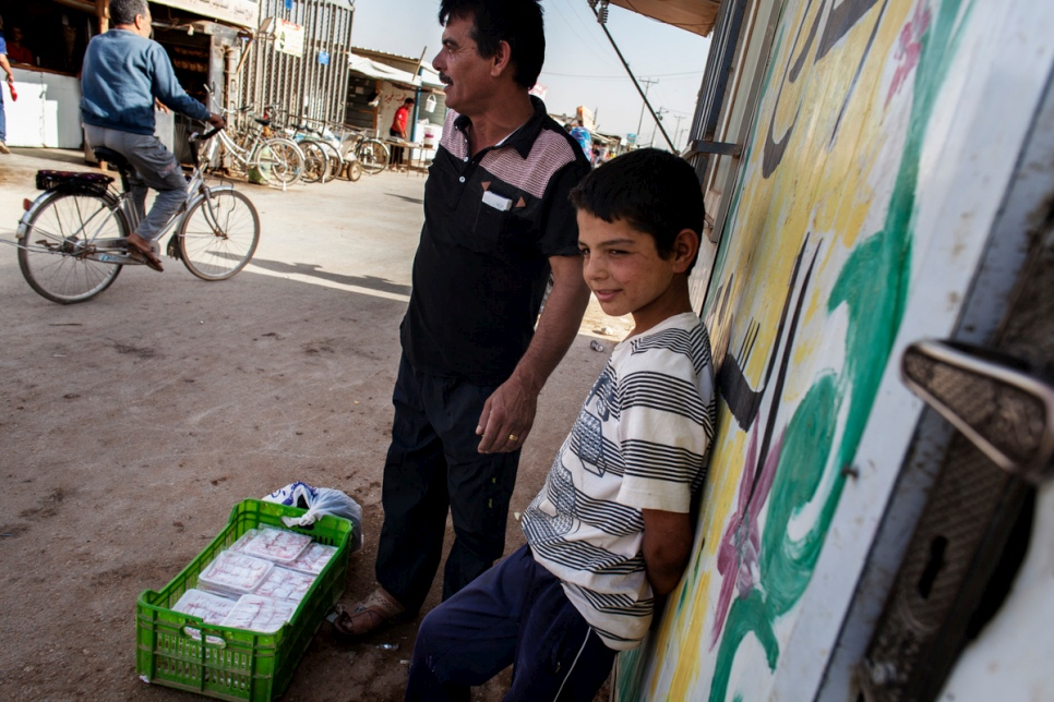 "Faris and his father, Abu Rabee', wait for customers to buy their handmade ""raha"" in the main shopping street at Za'atari refugee camp in Jordan."