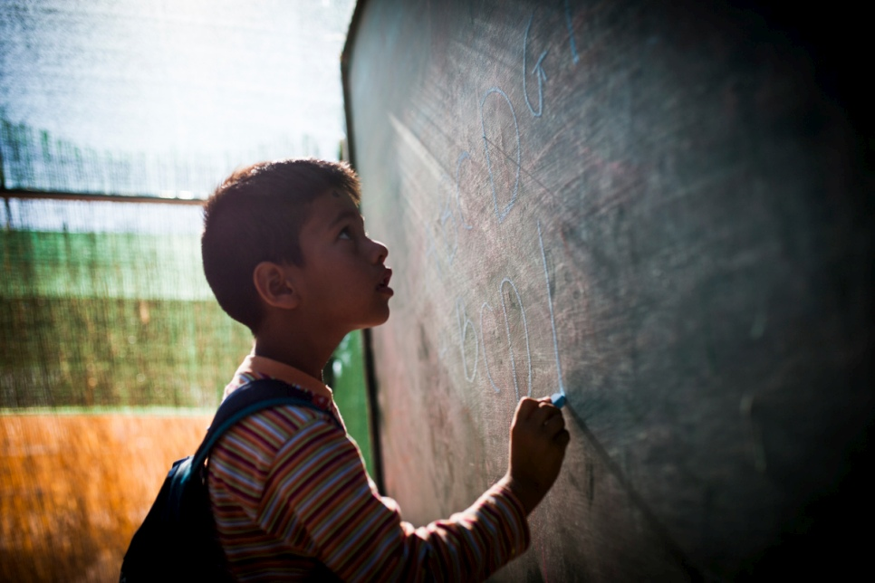 An Afghan boy spells out the Roman alphabet at a special English-language class at the Oinofyta reception centre in Greece.