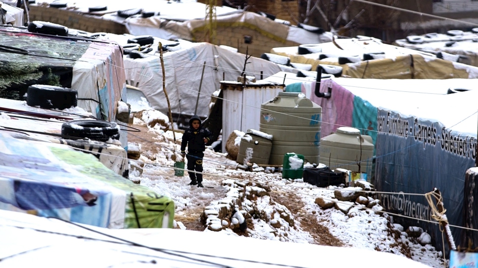A young Syrian refugee walks through snow at an informal settlement in Lebanon's Bekaa Valley.
