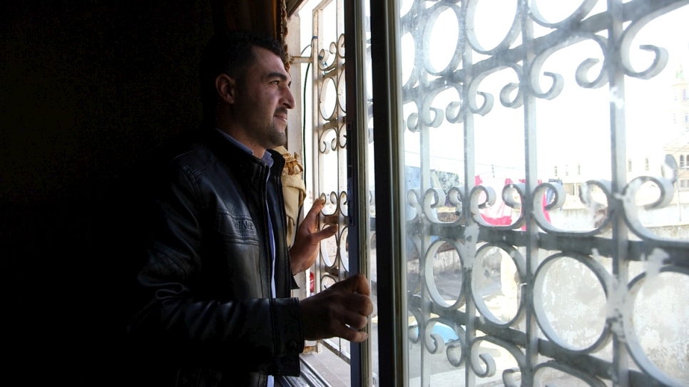Syrian refugee Firas al Ahmad, 30, looks out of the window at his father's house in Irbid, Jordan.