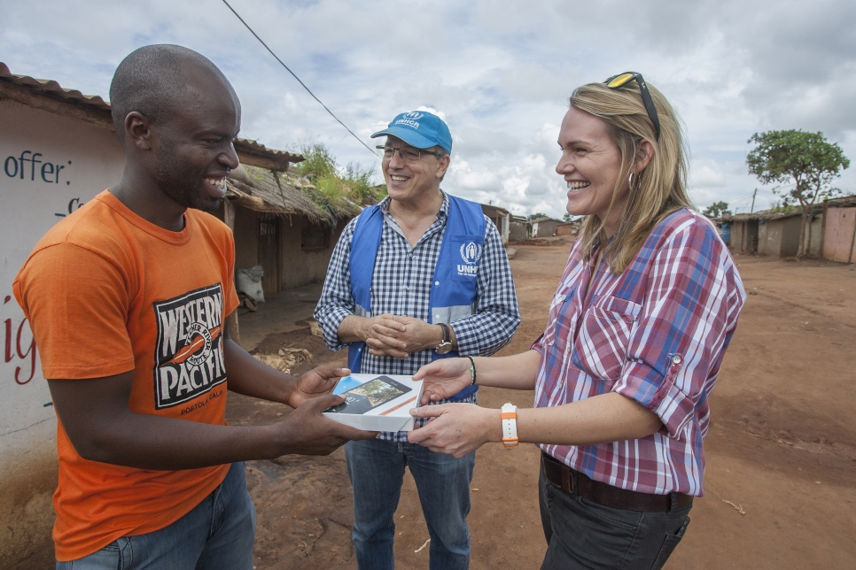 Remy Gakwaya, a 22 year old Burundian refugee receives a phone from Kate Krukiel, Director of Partnerships, Microsoft and Kamel Deriche of UNHCR. The phone is a donation from Microsoft to support the Connectivity for Refugees project in Dzaleka Camp, Malawi.
